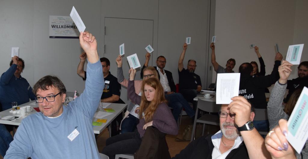Symbolfoto Abstimmung - menschen halten Stimmkarten hoch